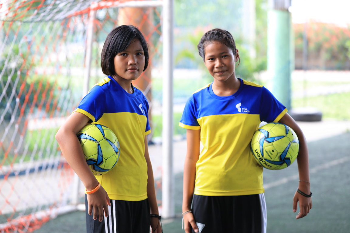 Nichada Hanchengchai, left, and Jennapa Maksawat, both sixth-grade students at Wat Yaichomprasat School, are pictured during a football clinic organized by Thai Union and Samut Sakhon Football Club